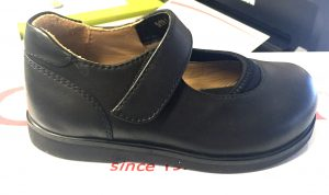 A small pair of black Mary Jane styles shoes.